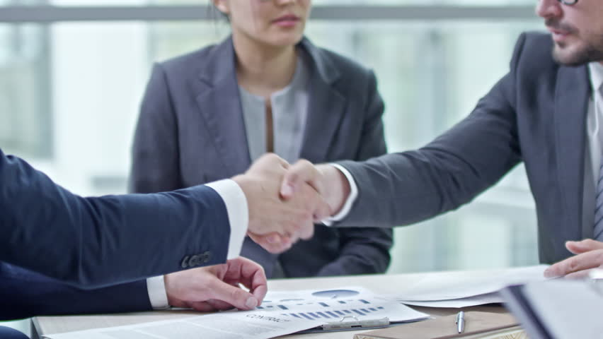 PAN with mid-section of bearded businessman in suit and his male business partner in glasses reading contracts, then shaking hands as female Asian corporate lawyer talking and asking questions