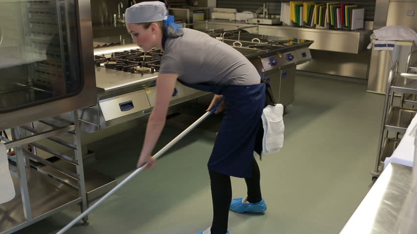 Cleaner cleaning the kitchen and wiping the floor with a mop