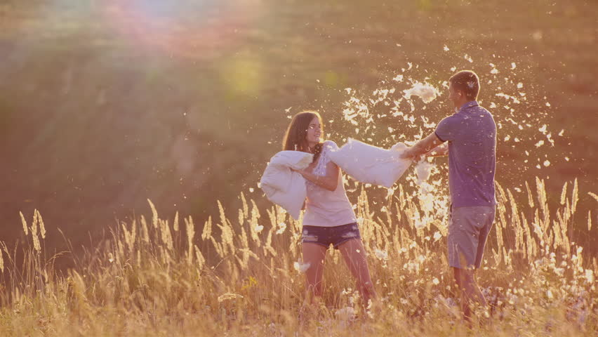 Young couple are madly having fun. A woman is beating her pillow with a friend, feathers are flying. Fight against the pillows, youth energy