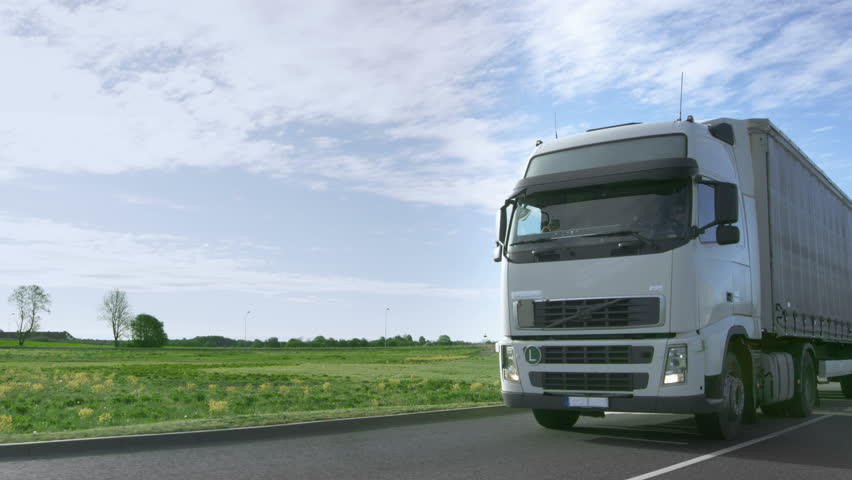 Frontal View of Speeding White Semi Truck with Cargo Trailer Drives on the Highway with Fields and Industrial Warehouses in the Background. Shot on RED EPIC-W 8K Helium Cinema Camera. #29799943
