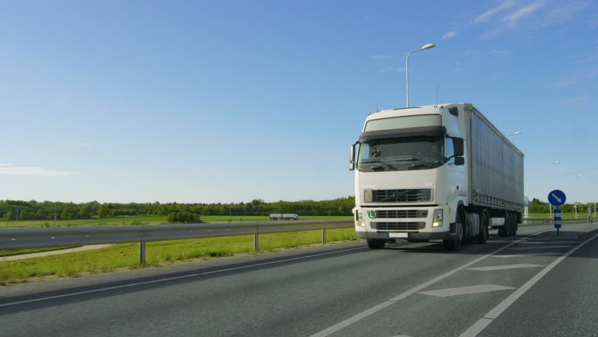 Big White Semi Truck with Cargo Trailer Drives on the Industrial Area Empty Road With Sun Shining in the Background. Shot on RED EPIC-W 8K Helium Cinema Camera.   Shutterstock HD Video #29799973