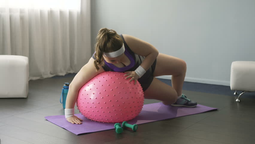 Overweight lady trying to train, funny attempts to lie on big fitness ball