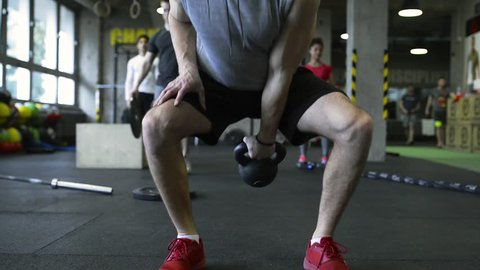 Young people in crossfit gym exercising, man lifting kettlebell