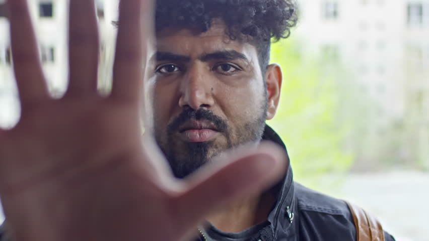 Close up of serious Arab man with beard looking into camera, the reaching hand and flashing his palm in stop gesture