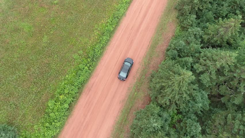 Black car driving down red dirt road with forest on both sides opening up to the ocean | Shutterstock HD Video #29841178