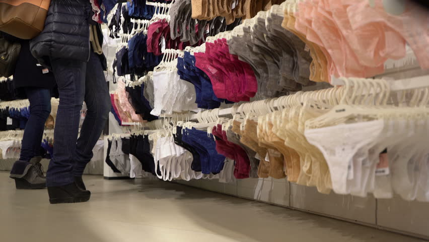 Concept women's underwear shop in mall. Girl chooses panties and bra. Panties, bras hang on hangers. Concept of shop of intimate clothes. Low angle view real time