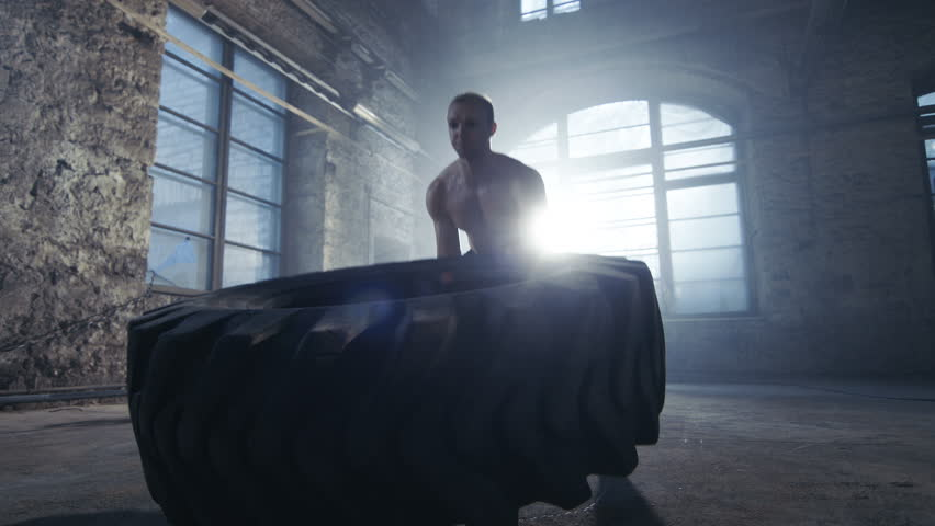 Strong Muscular Man Lifts/ Flips Tire as Part of His Bodybuilding/ Cross Fitness Training. He's Covered in Sweat and Works out in a Abandoned Factory Remodeled into Gym. Shot on RED EPIC-W 8K  Camera.