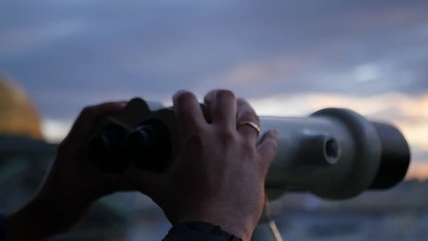 Holding binoculars in hands on sunset background, close-up. slow motion, 1920x1080, full hd