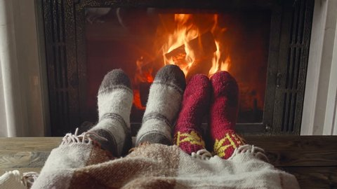 Closeup 4k footage of couple in love wearing woolen socks relaxing by the fireplace at chalet. Toned video