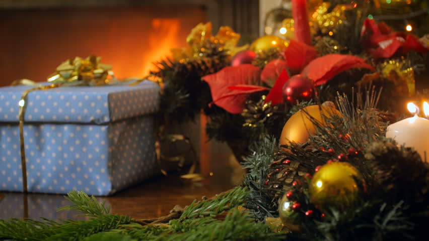 4k video from slider of advent wreath with burning candles against Christmas gifts and fireplace at house