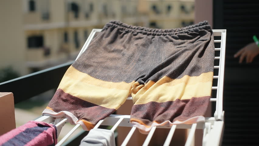 A man putting beachwear clothes on a drying rack or dryer. Angled shot.  | Shutterstock HD Video #29954143