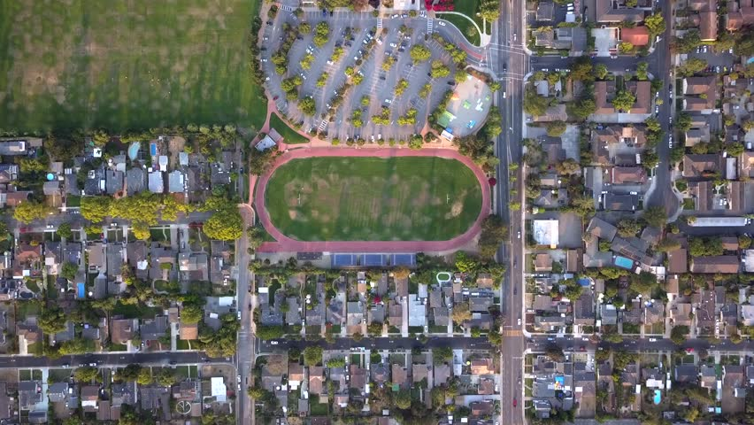 Ariel view of a running track flying down on top of it, Ariel view of people running around a track with houses, and cars driving by, time lapse of people running around a track, Track season. Birds.  | Shutterstock HD Video #29964673