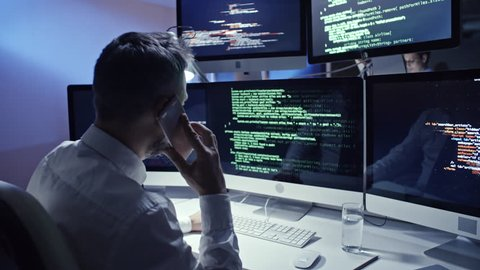 Experienced male programmer working on multi-screen computer in office at  night and making a phone call