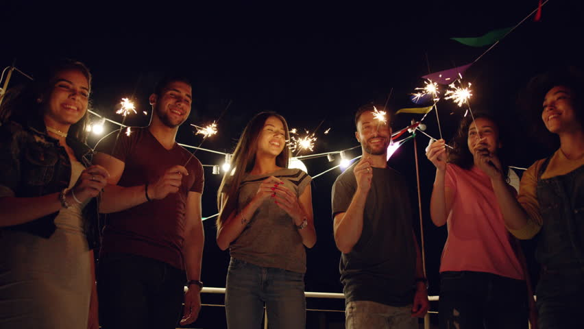 Diverse Young Party People On Rooftop Happy Dancing With Sparkler Fire Laughing And Dancing Happy Fun Time Freedom To Enjoy Life Concept During Beautiful Urban Night Shot on Red Epic W 8K Slow Motion