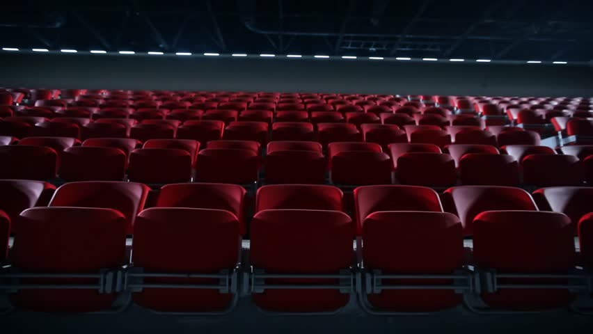 Camera dollies out to reveal empty seats in a basketball