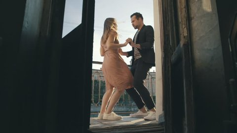 Cheerful couple dancing at a party on a summer day. Man and woman dancing at a party in balcony slow motion. Loving couple having fun at a party on a sunny evening full length view