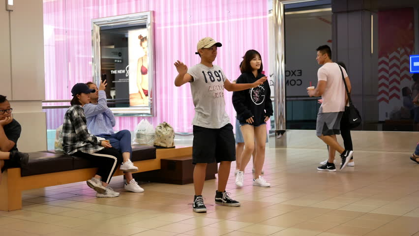 Burnaby, BC, Canada - August 16, 2017 : Motion of young people dancing with Xbox demonstrated game beside Microsoft store with 4k resolution