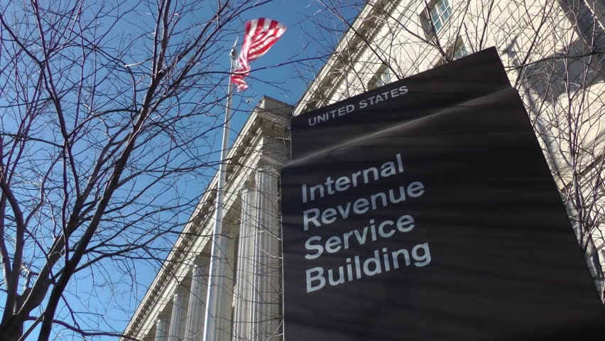 Internal Revenue Service - IRS - headquarters in Washington, DC. Sign with American flag flying above. | Shutterstock HD Video #3003994