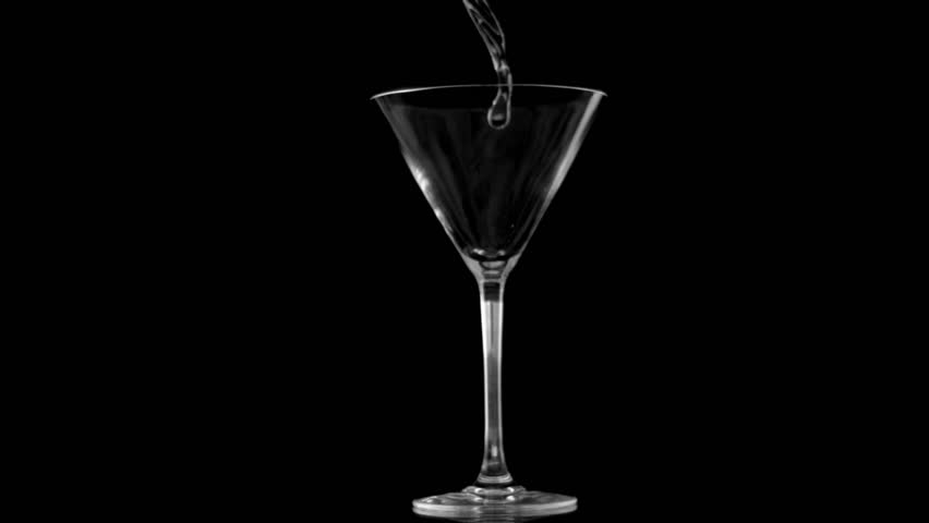 Vodka being poured in super slow motion in glass against black background