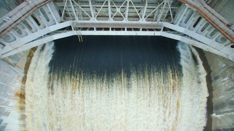 Powerful stream of water falls from the shutter in the dam, hydroelectric