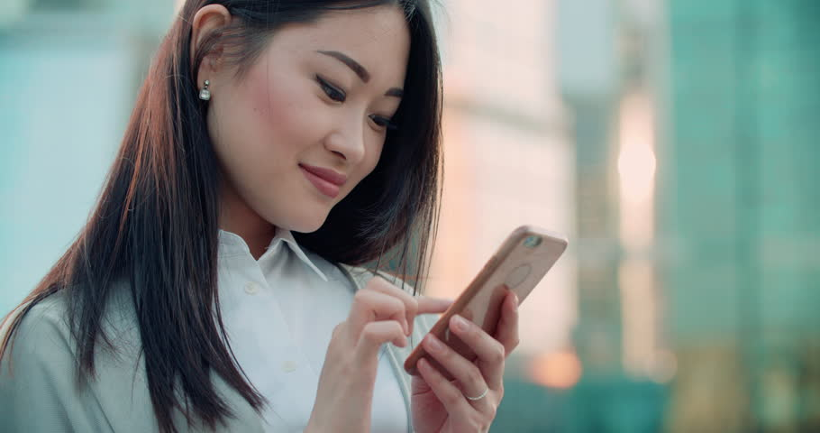 closeup of beautiful young business Asian woman with smartphone texting messenger with skyscrapers in the background