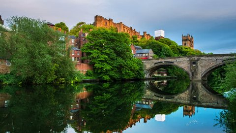 Durham, UK. Illuminated Castle and University in Durham, UK. Popular landmarks in the evening. Time-lapse of a sunset with reflection in the river and historical bridge