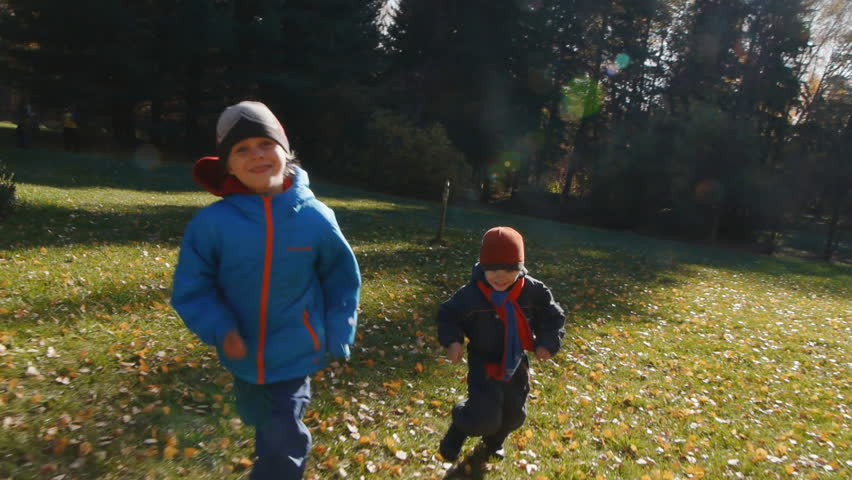 cheerful boys having fun in fall forest