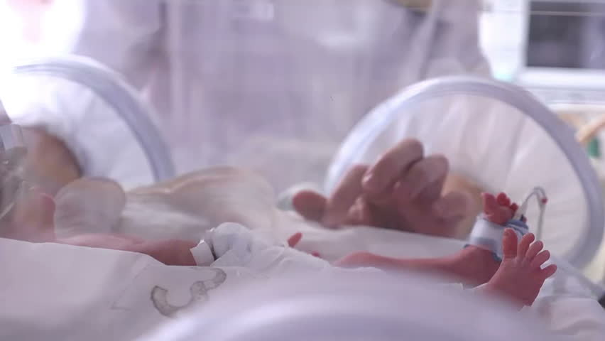 A newborn in incubator, intensive hospital therapy: CCU, ICU, ITU. The tiny baby child moves his fingers, foot and leg vigorously., Closeup