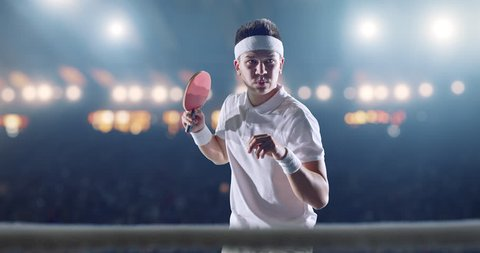 Ping pong player in action on a professional sports arena. He is wearing unbranded clothes.