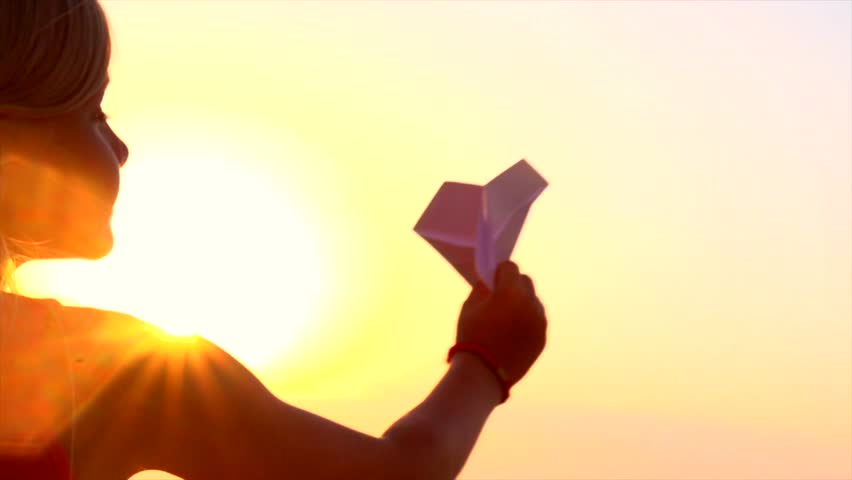 Happy Child playing with paper airplane over sunset background. Slow motion video footage 240 fps. 4K UHD video. High speed camera