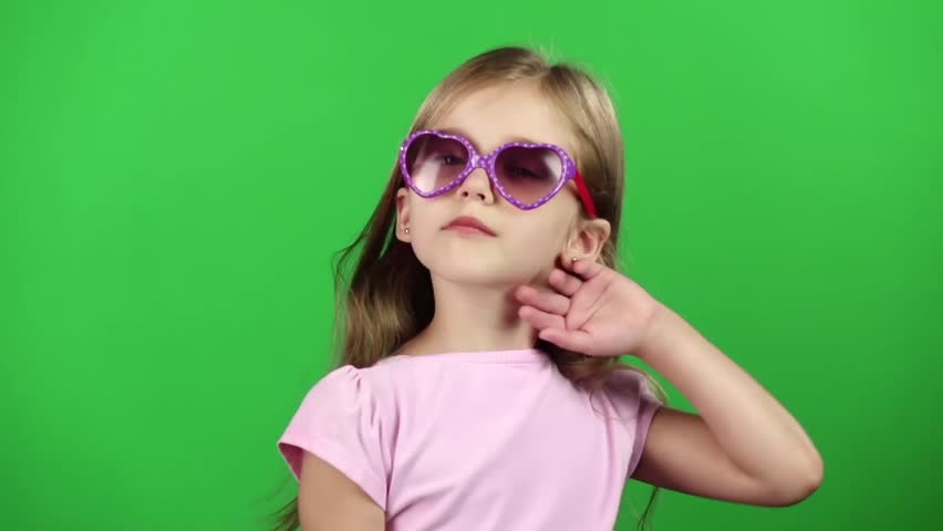 Child posing for video cameras with glasses. Green screen. Slow motion