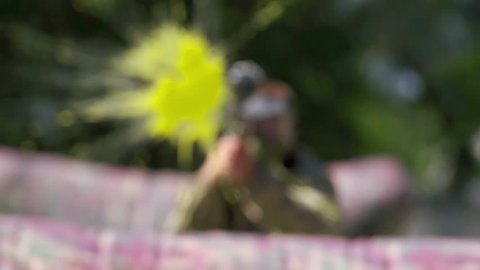 Paintball player aiming and shooting target HD game slow-motion POV video. Man with gun hitting to camera on playing field. Ball flying and painting camera