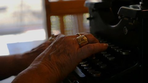 A woman typing on an antique manual typewriter