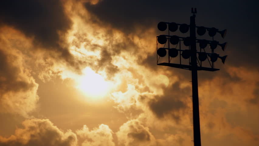 Timelapse of sun setting behind a cloudscape and a silhouetted stadium light. | Shutterstock HD Video #3020233
