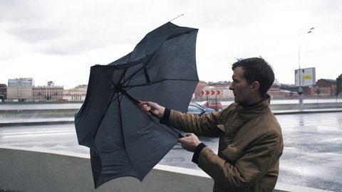 Man in jacket with umbrella standing outdoors. The gust of wind pulls umbrella out of hand