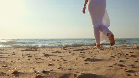 Legs of caucasian girl wearing white long dress and silver bracelets walking barefoot sand on sea beach, sun, lens, flare. Slow motion. Woman walks away camera