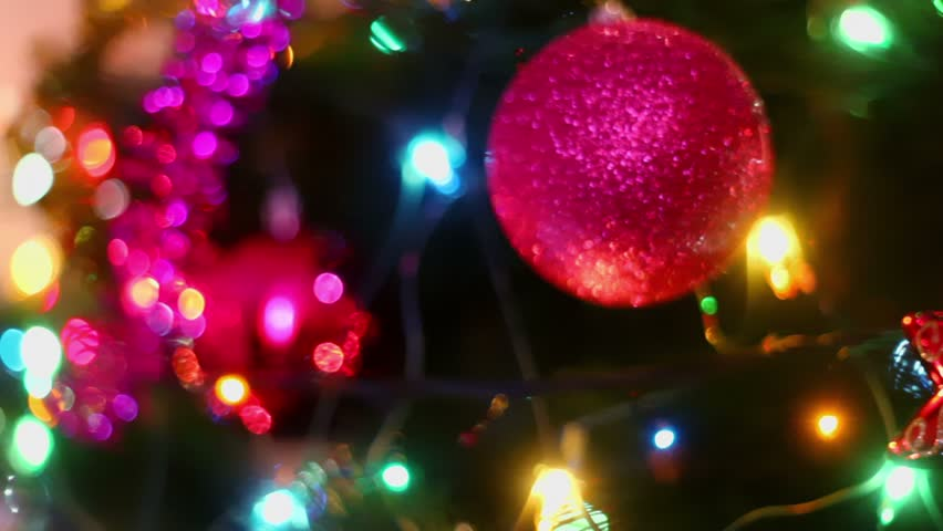 Colorful adornment with garland on fir tree, closeup view in motion