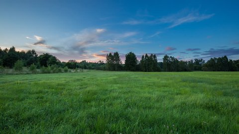 4k time lapse landscape with sunset sky over green meadow. 3840x2160