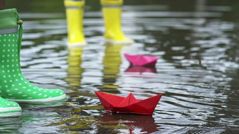 Tilt down of little African-American girl with curly hair wearing raincoat and rubber boots putting red origami paper boat in puddle