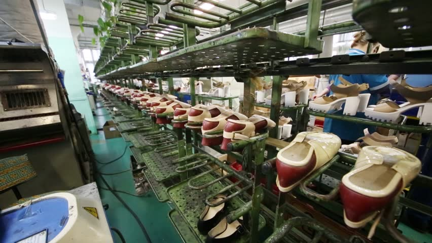 Female shoes are on conveyor in shoes factory, people out of focus