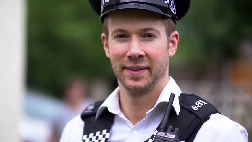 Portrait Of A Police Officer, Happy and Friendly, Close Up in Slow Motion. Wearing Black and White Uniform Including Hat. White Caucasian in 30's.