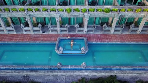 Young woman enjoying a pool at villa, aerial movie from the drone camera
