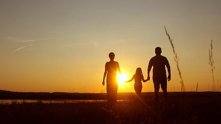 silhouette happy child with mother and father family at sunset summertime concept