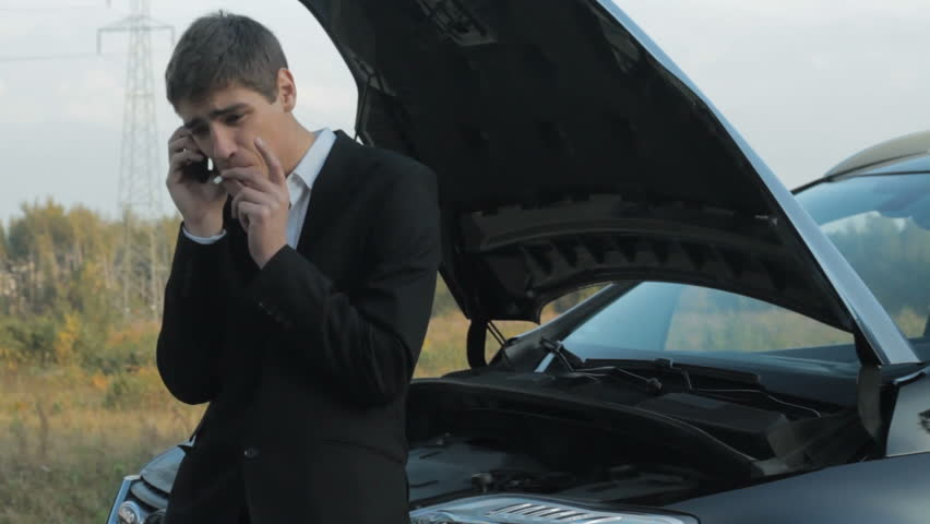 Young businessman smoking cigarettes and talking on the phone next to broken car
