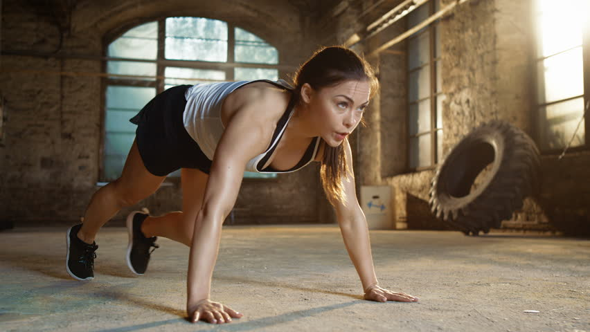 Athletic Beautiful Woman Does Running Plank as Part of Her Cross Fitness, Bodybuilding Gym Training Routine. Shot on RED EPIC-W 8K Helium Cinema Camera.