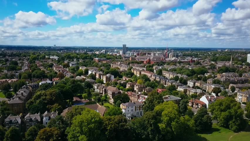 Aerial view of a leafy UK suburb on a summers day - camera still - then tracks right