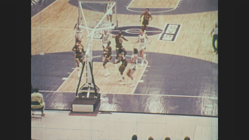 1970s: Teams play basketball. Feet in sneakers run on basketball court. Woman figure skates in ice rink. Woman falls on ice. Man slips in water while playing soccer. Man crashes while water skiing