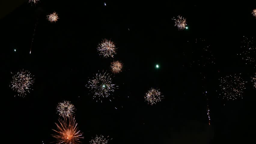 Ungraded: Fireworks show. Colorful fireworks at city celebration explode in night sky on background of clouds and smoke. Ungraded H.264 from camera without re-encoding. (av41013u)