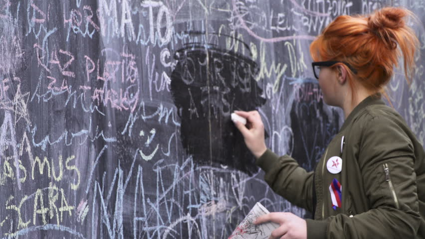 Prague, CZ - 17 November 2016: A young Red Hair Woman write on a black board, The opportunity for people to make a statement about societal issues in a creative manner. Editorial Documentary | Shutterstock HD Video #30369793