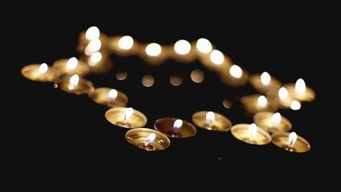 Movie of burning candles in the shape of a star of david on a black background. Bokeh on dark backdrop, shallow depth of field